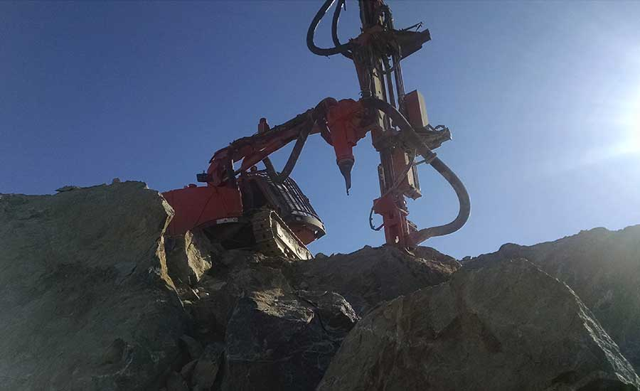 drilling rig on rock outcropping